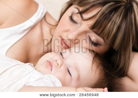 Lovely mother with her little daughter sleeping in bed. Focus on baby
