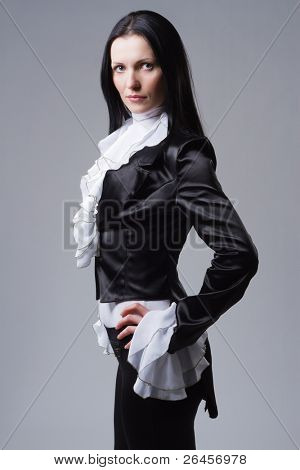 Elegant woman in tailcoat against gray background