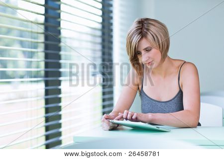 Pretty, young businesswoman/college student using her tablet computer (shallow DOF; color toned image)