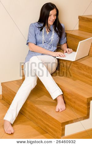 Home living happy woman with laptop sitting on stairs