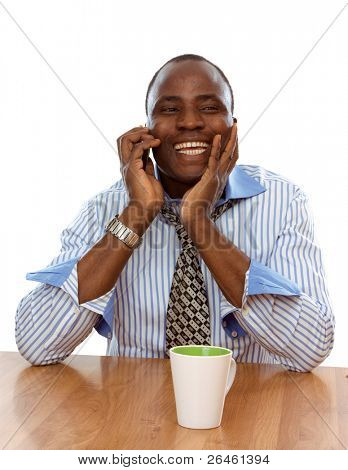 Afro man sitting on the desk and talking on the phone, isolated on white background