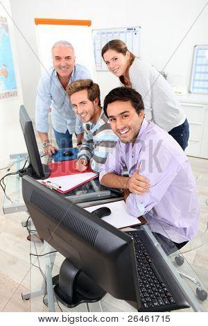 Cuatro personas sonrientes se reunieron alrededor de una computadora en un aula