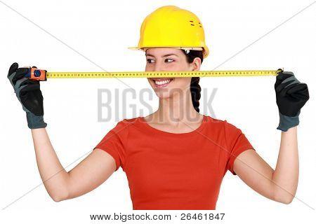 Tradeswoman extending a measuring tape