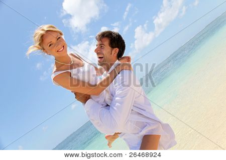Groom and bride laughing on a sandy beach