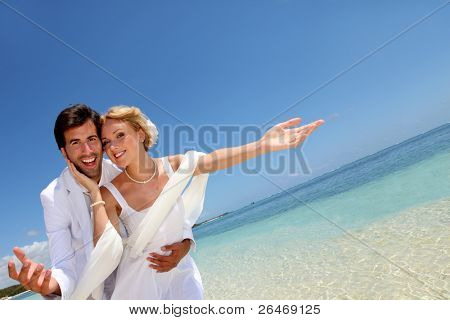 Married couple standing by blue lagoon
