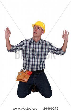 craftsman on his knees hands up