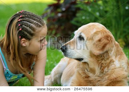 Little girl hugging a big  dog in an outdoor setting