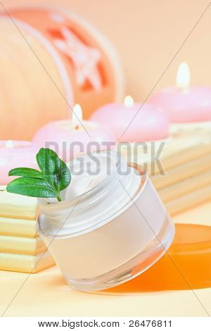Moisturizing cream with candles and towel
