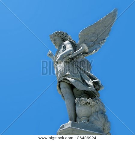 Winged angel statue against blue sky