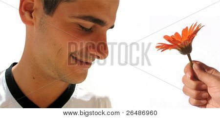 Profile of young handsome boy smiling with hand giving a flower - isolated