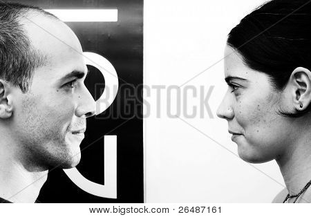 Eye contact - opposites. Portrait of a young couple face to face - b&w version