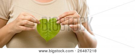 Care for the plants - girl hands holding a heart shaped green leaf