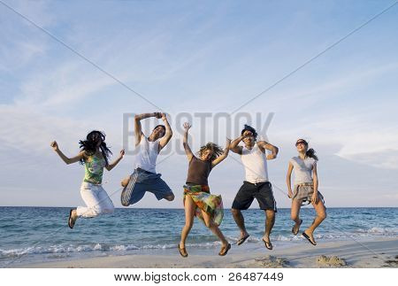 Group of five friends jumping on the beach