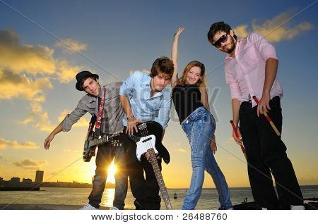 Portrait of young musical band posing outdoors at sunset with instruments
