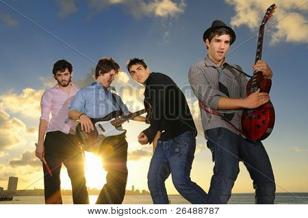 Group of young male musicians posing outdoors at sunset with instruments