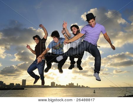 Group of four young males jumping against blue sky background