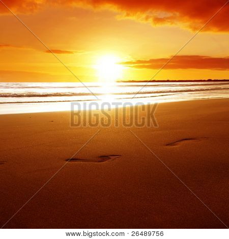 Footprints on the beach at sunset.