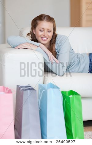 Smiling young woman taking a moment off on her couch after shopping touch