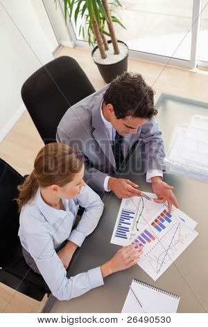 Above view of young consultant analyzing diagram with her client