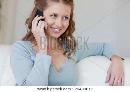 Young woman sitting on the sofa listening to caller