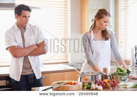 Young man watches his girlfriend cooking