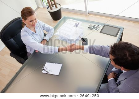 Above view of young consultant shaking hands with her client