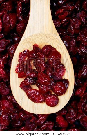 Dried cranberry fruit, food ingredient in wooden spoon