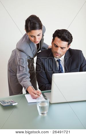 Portrait of a good looking business team working with a laptop in an office