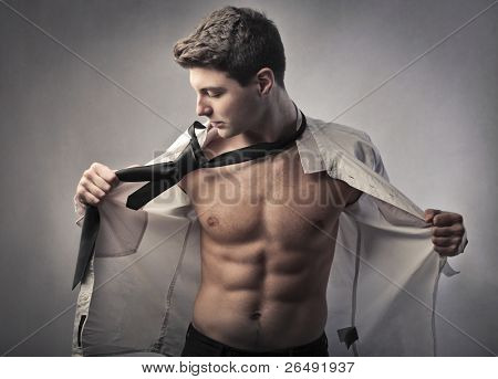 Handsome young businessman putting on his skirt and tie