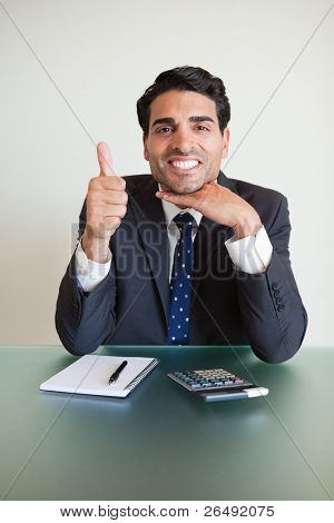 Portrait of an accountant with the thumb up in his office