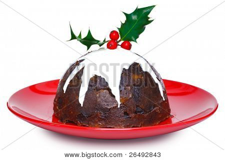 Photo of a steamed Christmas pudding with cream and holly on top isolated on a white background. Slight motion blur on the cream.