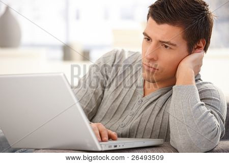 Portrait of goodlooking man focusing on laptop computer screen, typing on keyboard, looking serious.?