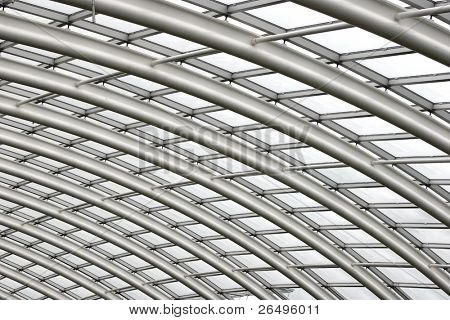 Section of the curved reinforced steel roof joists in a conservatory with glass panes in between.
