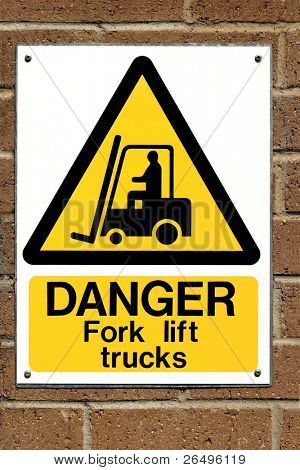 Fork lift truck operating warning sign fixed to a brick wall.