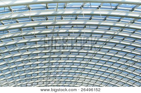 Curved reinforced steel roof joists in a conservatory roof, with glass panes in between and blue sky beyond.