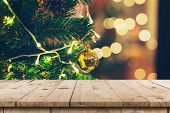 Empty Wood Table And Christmas Pine Cones Hanging From Christmas Tree With Display Montage For Produ poster