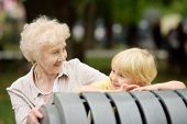 Beautiful Granny And Her Little Grandchild Together In Park. Grandma And Grandson Seating On The Ben poster