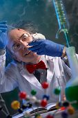 Crazy scientist with mad look  holding lab mouse for doing experiment poster
