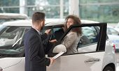 Car Dealer Standing With Client Near Car And Giving Keys. Beautiful Happy Woman Holding Hand And Tak poster