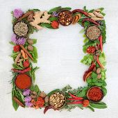 Herb leaf and spice wreath with a selection of fresh herbs and spices with flowers on rustic white w poster