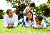 stock photo of family fun  - happy family smiling in a portrait of a mum and dad with their two kids - JPG