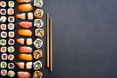 Top view of nigiri, hosomaki, uramaki and wooden chopsticks on black stone. High angle view of sushi poster