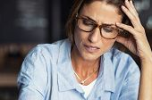 Portrait of stressed mature woman with hand on head looking down. Worried woman wearing spectacles.  poster