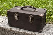 Old Used Weathered Vintage Grunge Suitcase On Stone Pavement Closeup In House Backyard poster