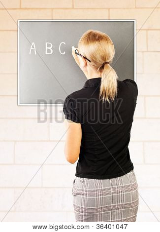 Young teacher write on blackboard, smart woman teaching pupil, rear view of educator explaining homework, beautiful young female professor standing near chalkboard in classroom, education concept