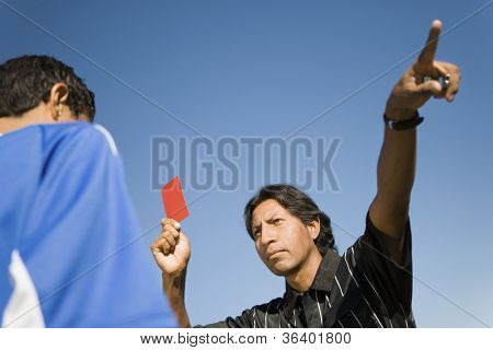 Low angle view of soccer referee pointing dismissal of player with red card