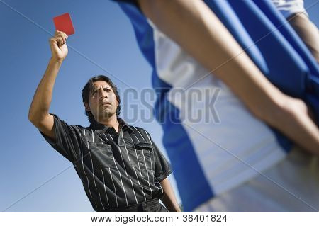 Referee indicating red card dismissal to player