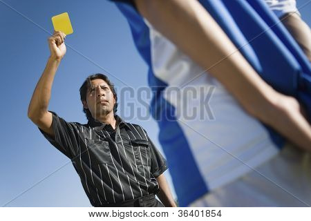 Low angle view of a soccer referee showing a yellow card