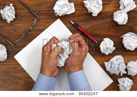 Crumpled paper and businessman tearing up another paper ball for the pile