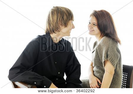 A young teenage couple enjoying a close conversation with each other.  On a white background.